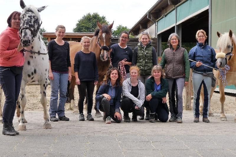 Eine Gruppe von Teilnehmerinnen der Jahresgruppe präsentiert sich mit zwei Pferden