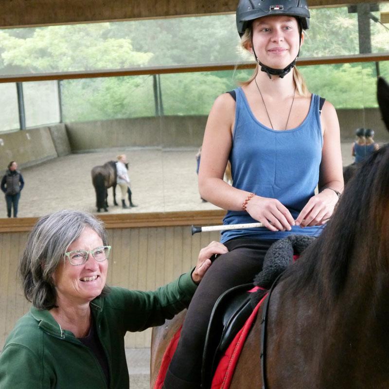 Reiterin sitzt auf Pferd, Anja erläutert den Hüftbeuger
